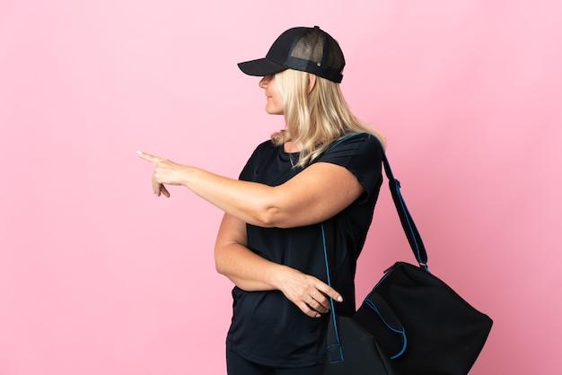 Middelbare leeftijd vrouw met sporttas geïsoleerd op roze muur terug te wijzen