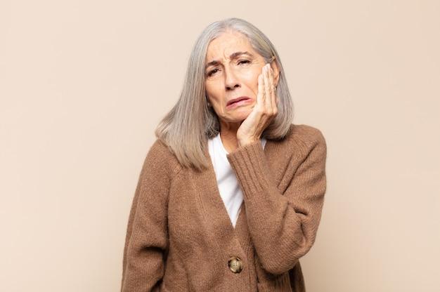 Middelbare leeftijd vrouw met wang en pijnlijke kiespijn lijden