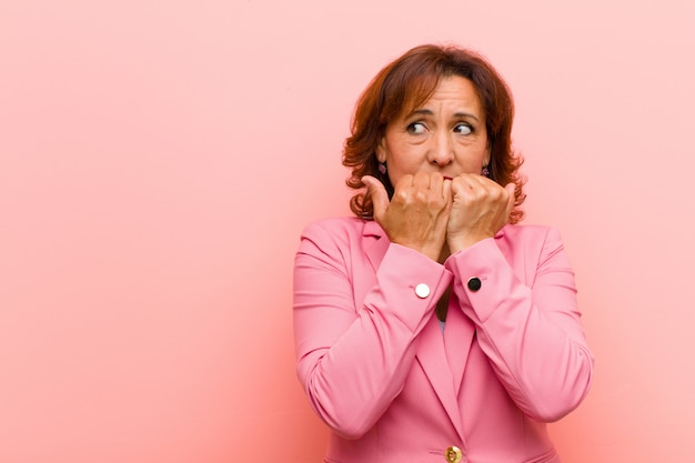 Middelbare leeftijd vrouw op zoek bezorgd, angstig, gestrest en bang, nagels bijten en op zoek naar laterale kopie ruimte