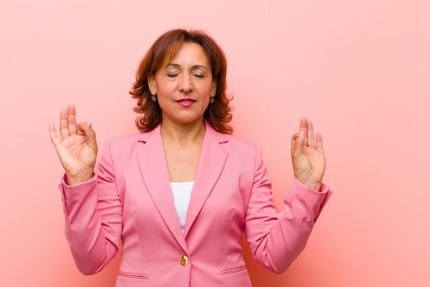 Middelbare leeftijd vrouw op zoek geconcentreerd en mediteren, tevreden en ontspannen voelen, denken of een keuze maken tegen roze muur