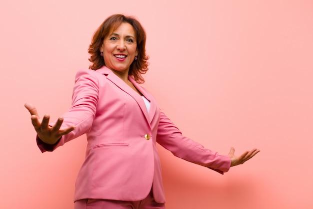 Middelbare leeftijd vrouw op zoek gelukkig, arrogant, trots en zelf tevreden, gevoel als een nummer een roze muur