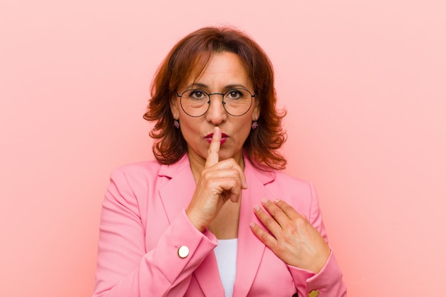 Middelbare leeftijd vrouw op zoek serieus en kruis met vinger tegen lippen gedrukt eist stilte of stil, geheimhoudend