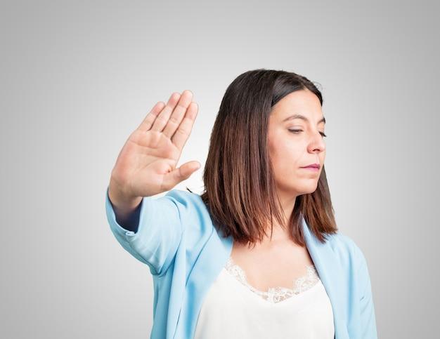 Middelbare leeftijd vrouw serieus en vastberaden, hand in de voorkant, stop gebaar, ontkennen concept