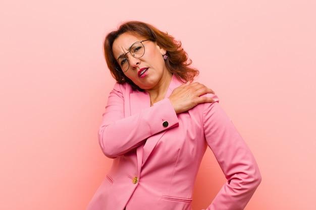 Middelbare leeftijd vrouw voelt zich moe, gestrest, angstig, gefrustreerd en depressief, lijdt aan rug of nekpijn roze muur