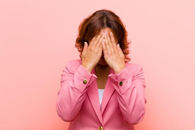 Middelbare leeftijd vrouw voelt zich verdrietig, gefrustreerd, nerveus en depressief, bedekkend gezicht met beide handen, huilend tegen roze muur