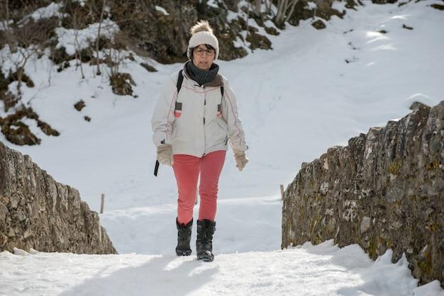 Middelbare leeftijd vrouw wandelen in de sneeuw