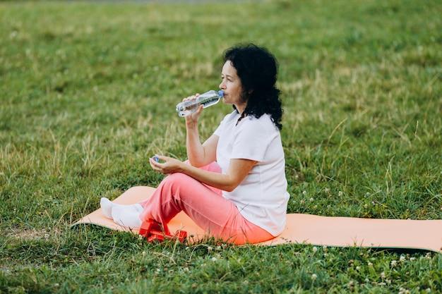 Middelbare leeftijd vrouw zitten in de yogamat en drinkwater na fitness