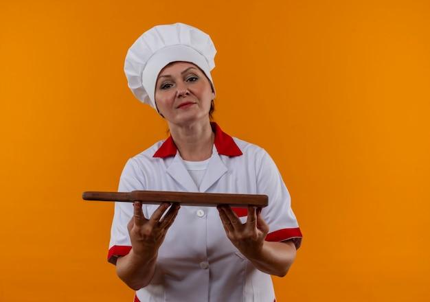 Middelbare leeftijd vrouwelijke kok in chef-kok uniforme snijplank houden op geïsoleerde gele muur met kopie ruimte