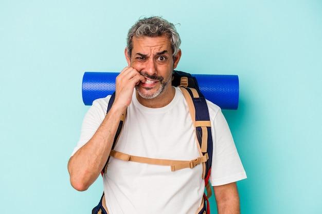 Middelbare leeftijd wandelaar blanke man geïsoleerd op blauwe achtergrond vingernagels bijten, nerveus en erg angstig.
