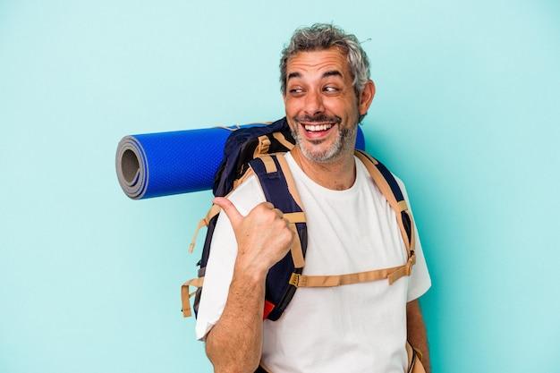 Middelbare leeftijd wandelaar blanke man geïsoleerd op blauwe achtergrond wijst met duimvinger weg, lachend en zorgeloos.