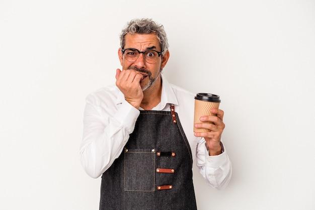 Middelbare leeftijd winkelbediende met een take-away koffie geïsoleerd op een witte achtergrond vingernagels bijten, nerveus en erg angstig.