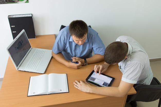 Middelbare leeftijd zakenlieden aan de tafel druk bezig met browsen met behulp van tablet pc. gevangen in luchtfoto.