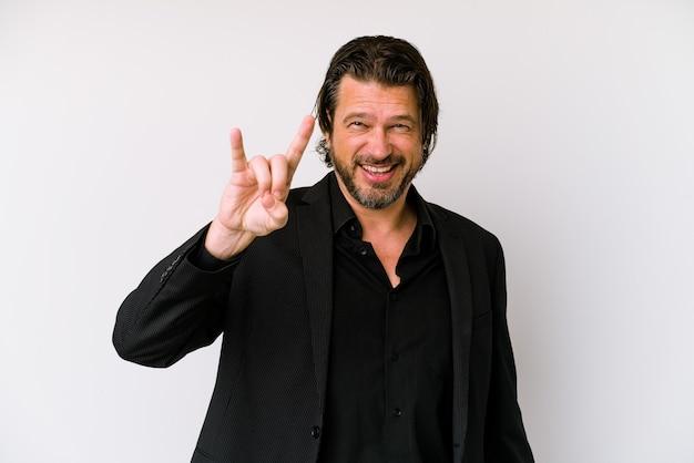 Middelbare leeftijd zakenman geïsoleerd op een witte muur met een hoorns gebaar