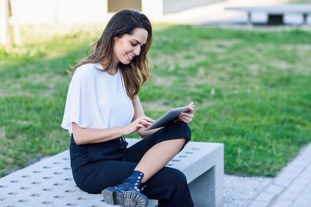 Middelbare leeftijdsvrouw die digitale tabletzitting in openlucht op stedelijke achtergrond gebruiken.