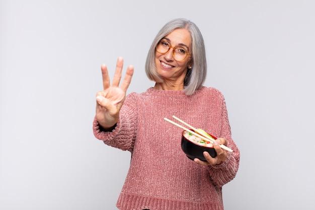 Middelbare leeftijdsvrouw die en vriendschappelijk geïsoleerd glimlacht kijkt