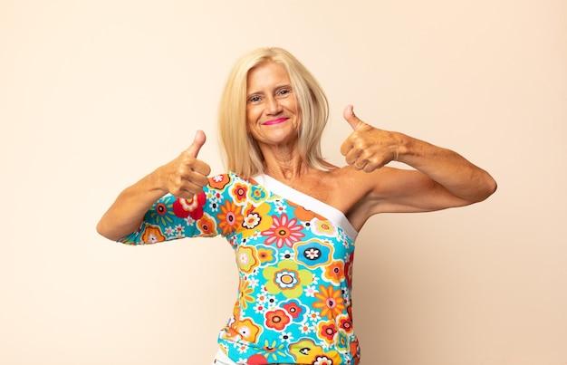 Middelbare leeftijdsvrouw die in grote lijnen gelukkig, positief, zelfverzekerd en succesvol kijkt, met beide duimen omhoog