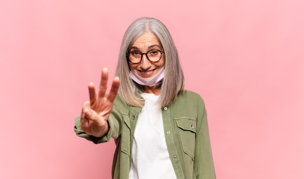 Middelbare leeftijdsvrouw die vriendelijk glimlacht kijkt en nummer drie of derde met vooruit aftellende hand toont
