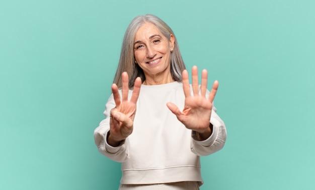 Middelbare leeftijdsvrouw die vriendelijk glimlacht kijkt, nummer acht of achtste met vooruit hand toont, aftellend