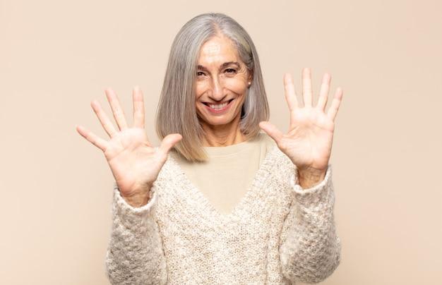 Middelbare leeftijdsvrouw die vriendelijk glimlacht kijkt, nummer tien of tiende met vooruit hand toont, aftellend