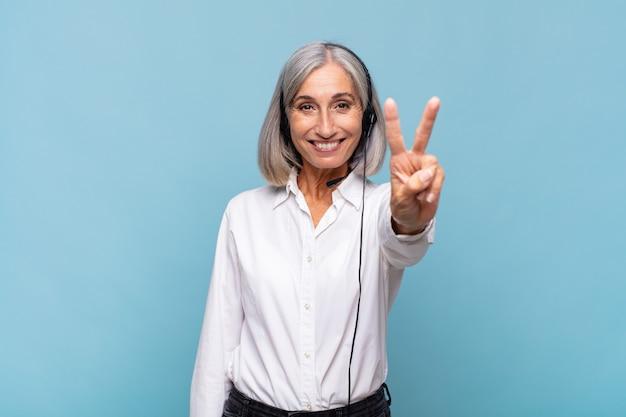 Middelbare leeftijdsvrouw die vriendelijk glimlacht kijkt, nummer twee of seconde met vooruit hand toont, aftellend. telemarketeer concept