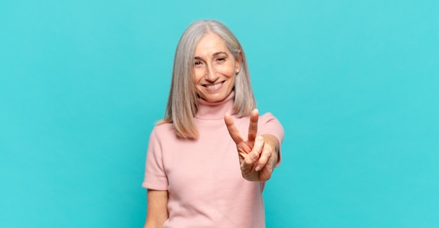 Middelbare leeftijdsvrouw die vriendelijk glimlacht kijkt, nummer twee of seconde met vooruit hand toont, aftellend