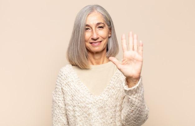 Middelbare leeftijdsvrouw die vriendelijk glimlacht kijkt, nummer vijf of vijfde met vooruit hand toont, aftellend