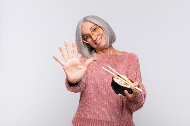 Middelbare leeftijdsvrouw die vriendelijk glimlacht kijkt, nummer vijf of vijfde met vooruit hand toont, die aziatisch voedselconcept aftelt