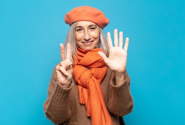 Middelbare leeftijdsvrouw die vriendelijk glimlacht kijkt, nummer zeven of zevende met vooruit hand toont, aftellend
