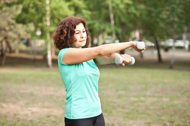 Middelbare oudere actieve vrouw die oefeningen doet met halters in een park buiten park