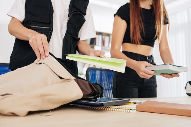 Middelbare scholieren boeken, tablets en voorbeeldenboeken in schooltassen zetten