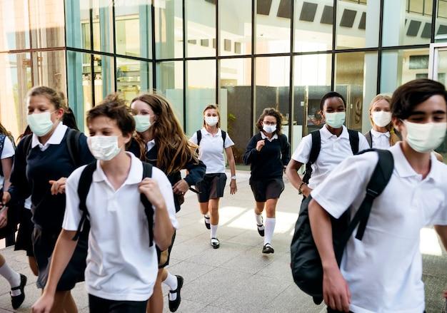 Middelbare scholieren met maskers op weg naar huis