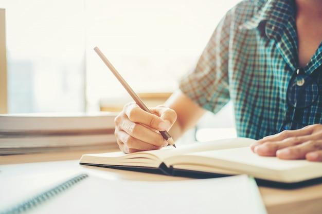 Middelbare school of hogeschoolstudent die in bibliotheek studeren en lezen