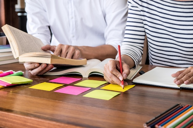 Middelbare school of studentengroep zit aan bureau in bibliotheek studeren en lezen, huiswerk en les praktijk