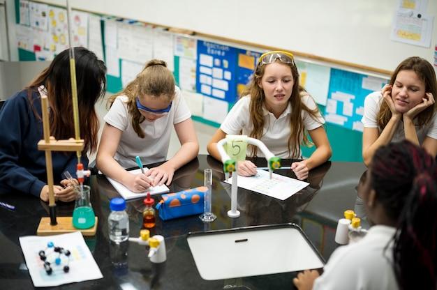 Middelbare schoolstudenten die in het klassenklasse van het chemielaboratorium bestuderen