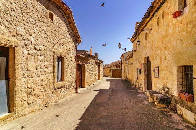 Middeleeuws dorp met stenen huizen, geplaveide straten, oude deuren en ramen, bogen en muren. maderuelo segovia spanje. vogel zwaluw vliegen.