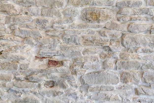 Middeleeuwse kasteel stane muurtextuur, oude stenen muurachtergrond van middeleeuws kasteel.