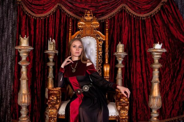 Middeleeuwse koningin in historische kledij op gouden troon in kasteel. portret van een jonge vrouw in een oude stijljurk op een antieke troon in de ontvangstruimte van het fort. concept van themakostuumevenementen