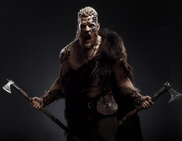 Middeleeuwse krijger viking met tattoo baard en vlechten in haar met bijl en schild