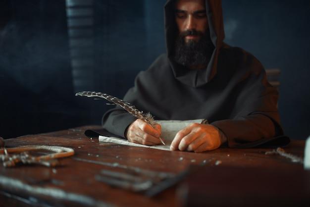 Middeleeuwse monnik aan tafel zitten en schrijven, bovenaanzicht