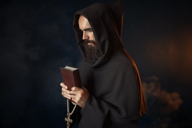 Middeleeuwse monnik bidden met boek en kruis in handen in de kerk, geheim ritueel. mysterieuze monnik in donkere cape. mysterie en spiritualiteit