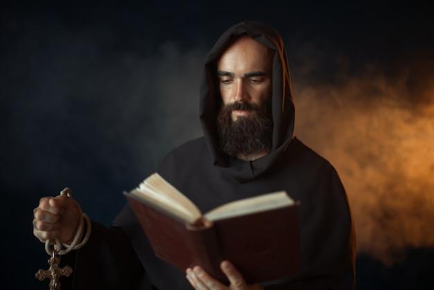 Middeleeuwse monnik bidden met boek in handen in de kerk, geheim ritueel. mysterieuze monnik in donkere cape. mysterie en spiritualiteit
