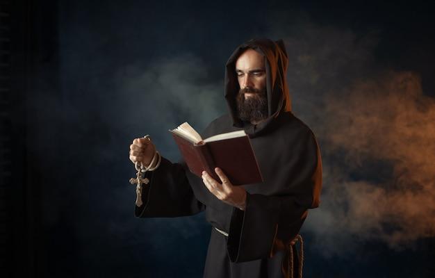 Middeleeuwse monnik die met boek in kerk bidt