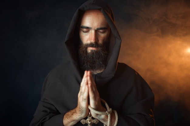 Middeleeuwse monnik die met gesloten ogen bidt