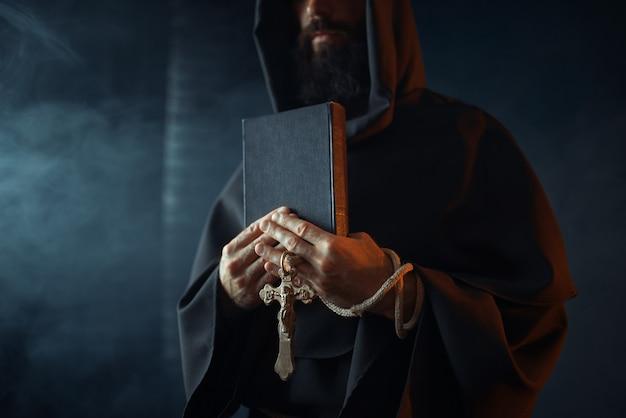 Middeleeuwse monnik houdt boek en houten kruis in handen