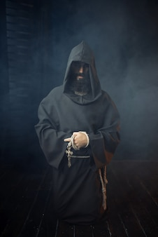 Middeleeuwse monnik houdt houten kruis in handen en bidden, religie. mysterieuze monnik in donkere cape. mysterie en spiritualiteit