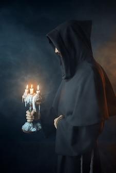 Middeleeuwse monnik in gewaad houdt een kandelaar in handen