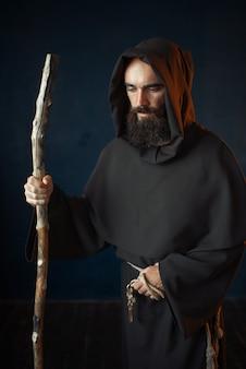 Middeleeuwse monnik in gewaad met kap rust op een stok