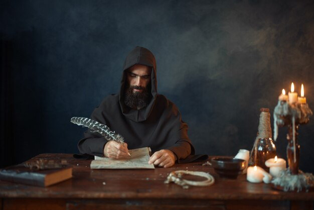Middeleeuwse monnik in gewaad schrijft met een ganzenveer