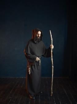 Middeleeuwse monnik in zwart gewaad met capuchon rust op een stok, religie. mysterieuze monnik in donkere cape