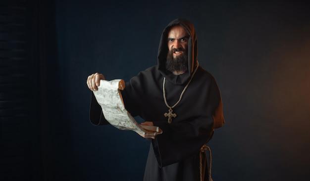 Middeleeuwse monnik met een boosaardig gezicht leest een gebed voor in het oude manuscript, religie. mysterieuze monnik in donkere cape. mysterie en spiritualiteit
